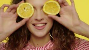 Ευτυχής γυναίκα που έχει τη διασκέδαση με τα μισά λεμονιών στο στούντιο Πρότυπο χαμόγελο προσώπου μόδας απόθεμα βίντεο