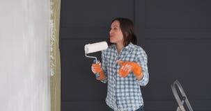 Ευτυχής γυναίκα που έχει τη διασκέδαση χρωματίζοντας το νέο τοίχο διαμερισμάτων απόθεμα βίντεο