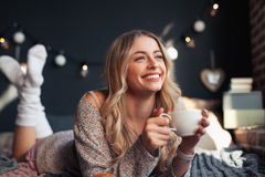 Ευτυχής γυναίκα που έχει το ζεστό ποτό στο κρεβάτι στοκ εικόνες