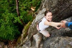 Ευτυχής γυναίκα που αναρριχείται στην οδοιπορία βράχου υπαίθρια Ξένοιαστος οδοιπόρος που χαμογελά το φίλο της Άτομο που βοηθά να  στοκ φωτογραφίες με δικαίωμα ελεύθερης χρήσης