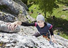 Ευτυχής γυναίκα που αναρριχείται στο βράχο Στοκ Φωτογραφίες