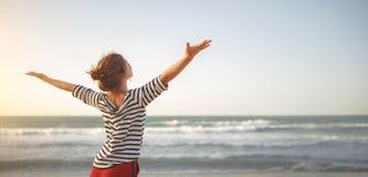 Ευτυχής γυναίκα που απολαμβάνει της ελευθερίας με τα ανοικτά χέρια στη θάλασσα στοκ εικόνα με δικαίωμα ελεύθερης χρήσης