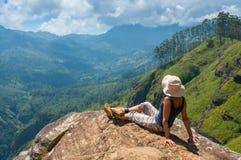 Ευτυχής γυναίκα που απολαμβάνει τη φύση πάνω από τον απότομο βράχο βουνών στοκ εικόνα
