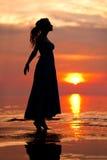 Ευτυχής γυναίκα που απολαμβάνει στο ηλιοβασίλεμα θάλασσας Σκιαγραφημένος ενάντια στους ήλιους Στοκ Εικόνες