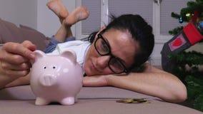 Ευτυχής γυναίκα που βρίσκεται στον καναπέ κοντά στη ρόδινη piggy τράπεζα απόθεμα βίντεο