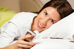 Ευτυχής γυναίκα που βρίσκεται στο χαμόγελο κρεβατιών, που διαβάζει ένα μήνυμα κειμένου στοκ εικόνες με δικαίωμα ελεύθερης χρήσης