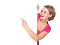 Ευτυχής γυναίκα που δείχνει με το δάχτυλό της στο έμβλημα Στοκ εικόνα με δικαίωμα ελεύθερης χρήσης