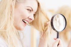 Ευτυχής γυναίκα που εξετάζει μέσω του magnifer την τρίχα στοκ εικόνες με δικαίωμα ελεύθερης χρήσης