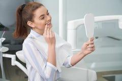 Ευτυχής γυναίκα που εξετάζει τον καθρέφτη στην κλινική οδοντιατρικής στοκ φωτογραφία με δικαίωμα ελεύθερης χρήσης