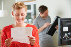 Ευτυχής γυναίκα που εξετάζει το Μπιλ για την εγκατάσταση TV Στοκ εικόνες με δικαίωμα ελεύθερης χρήσης