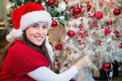 Ευτυχής γυναίκα που διακοσμεί το χριστουγεννιάτικο δέντρο Στοκ Εικόνα