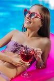 Ευτυχής γυναίκα που κάνει ηλιοθεραπεία στο στρώμα αέρα στη λίμνη στοκ εικόνα με δικαίωμα ελεύθερης χρήσης
