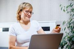 Ευτυχής γυναίκα που κάνει τις αγορές της χρησιμοποιώντας on-line μια πιστωτική κάρτα Στοκ Φωτογραφία