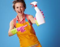 Ευτυχής γυναίκα που κλείνει το μάτι και που δείχνει στο μπουκάλι του απορρυπαντικού στο μπλε στοκ εικόνα με δικαίωμα ελεύθερης χρήσης