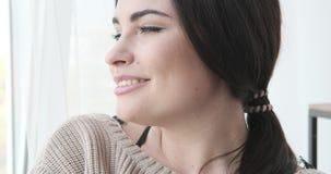 Ευτυχής γυναίκα που κοιτάζει έξω μέσω του παραθύρου φιλμ μικρού μήκους