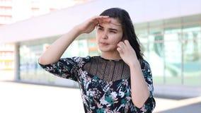 Ευτυχής γυναίκα που κοιτάζει μακριά, που κρατά το χέρι στο brow φιλμ μικρού μήκους