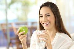 Ευτυχής γυναίκα που κρατά ένα μήλο και ένα ποτήρι του νερού στοκ φωτογραφία με δικαίωμα ελεύθερης χρήσης