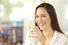 Ευτυχής γυναίκα που κρατά ένα ποτήρι του νερού στοκ φωτογραφία με δικαίωμα ελεύθερης χρήσης