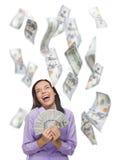 Ευτυχής γυναίκα που κρατά τους $100 Bill με πολλούς που πέφτουν γύρω Στοκ Εικόνες