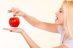 Ευτυχής γυναίκα που κρατά το εύγευστο κόκκινο μήλο Στοκ Εικόνες