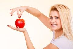 Ευτυχής γυναίκα που κρατά το εύγευστο κόκκινο μήλο Στοκ εικόνα με δικαίωμα ελεύθερης χρήσης