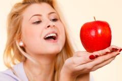 Ευτυχής γυναίκα που κρατά το εύγευστο κόκκινο μήλο Στοκ φωτογραφία με δικαίωμα ελεύθερης χρήσης