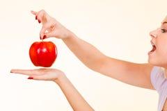Ευτυχής γυναίκα που κρατά το εύγευστο κόκκινο μήλο Στοκ Εικόνα