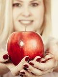 Ευτυχής γυναίκα που κρατά το εύγευστο κόκκινο μήλο Στοκ εικόνες με δικαίωμα ελεύθερης χρήσης