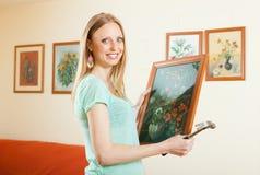 Ευτυχής γυναίκα που κρεμά την εικόνα τέχνης Στοκ Φωτογραφία