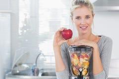 Ευτυχής γυναίκα που κλίνει στο σύνολο juicer φρούτων της και που κρατά το κόκκινο μήλο Στοκ Εικόνες