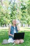 Ευτυχής γυναίκα που μεταφορτώνει τη μουσική υπαίθρια με το lap-top Στοκ Φωτογραφία