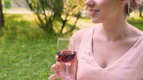 Ευτυχής γυναίκα που μιλά στους φίλους με τη διαθέσιμη συνεδρίαση χεριών γυαλιού κρασιού στο πάρκο, γεγονός απόθεμα βίντεο
