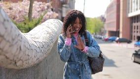 Ευτυχής γυναίκα που μιλά τηλεφωνικώς με το γέλιο στην πόλη φιλμ μικρού μήκους