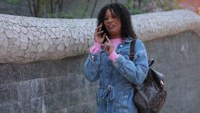 Ευτυχής γυναίκα που μιλά τηλεφωνικώς με το γέλιο στην πόλη απόθεμα βίντεο