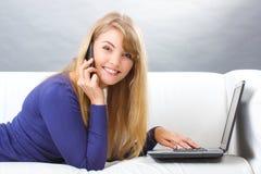 Ευτυχής γυναίκα που μιλά στο κινητό τηλέφωνο και που χρησιμοποιεί το lap-top που βρίσκεται στον καναπέ, σύγχρονη τεχνολογία Στοκ Φωτογραφίες