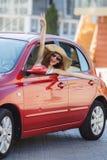 Ευτυχής γυναίκα που οδηγεί ένα κόκκινο συμπαγές αυτοκίνητο στοκ εικόνες