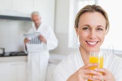 Ευτυχής γυναίκα που πίνει το χυμό από πορτοκάλι στο μπουρνούζι Στοκ φωτογραφία με δικαίωμα ελεύθερης χρήσης