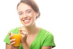 Ευτυχής γυναίκα που πίνει το χυμό από πορτοκάλι. Στοκ εικόνες με δικαίωμα ελεύθερης χρήσης