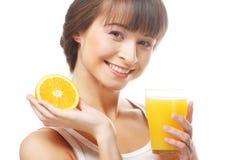 Ευτυχής γυναίκα που πίνει το χυμό από πορτοκάλι. Στοκ Εικόνα
