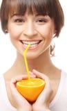 Ευτυχής γυναίκα που πίνει το χυμό από πορτοκάλι. Στοκ Εικόνες