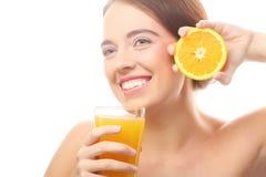 Ευτυχής γυναίκα που πίνει το χυμό από πορτοκάλι. Στοκ φωτογραφία με δικαίωμα ελεύθερης χρήσης