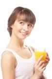 Ευτυχής γυναίκα που πίνει το χυμό από πορτοκάλι. Στοκ Φωτογραφίες