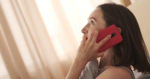 Ευτυχής γυναίκα που παίρνει το κινητό τηλέφωνο στο κρεβάτι απόθεμα βίντεο