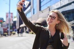 Ευτυχής γυναίκα που παίρνει selfie χρησιμοποιώντας την κινητή κάμερα στην πόλη στοκ φωτογραφίες με δικαίωμα ελεύθερης χρήσης