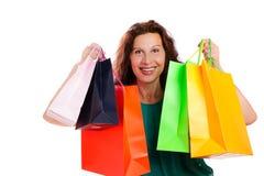 Ευτυχής γυναίκα που παρουσιάζει ζωηρόχρωμες τσάντες αγορών Στοκ εικόνα με δικαίωμα ελεύθερης χρήσης