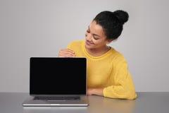 Ευτυχής γυναίκα που παρουσιάζει κενή μαύρη οθόνη comuter στοκ εικόνα