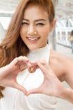 Ευτυχής γυναίκα που παρουσιάζει σημάδι χεριών καρδιών Στοκ Εικόνες
