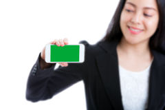 Ευτυχής γυναίκα που παρουσιάζει στο κενό έξυπνο τηλέφωνο πράσινη οθόνη στην άσπρη πλάτη Στοκ Εικόνα