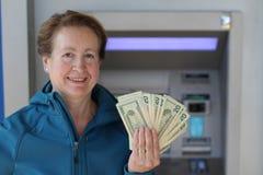 Ευτυχής γυναίκα που παρουσιάζει χρήματά της στο ATM Στοκ εικόνα με δικαίωμα ελεύθερης χρήσης