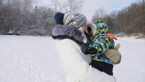 Ευτυχής γυναίκα που περιβάλλει την λίγος γιος στη χιονώδη χειμερινή ημέρα απόθεμα βίντεο